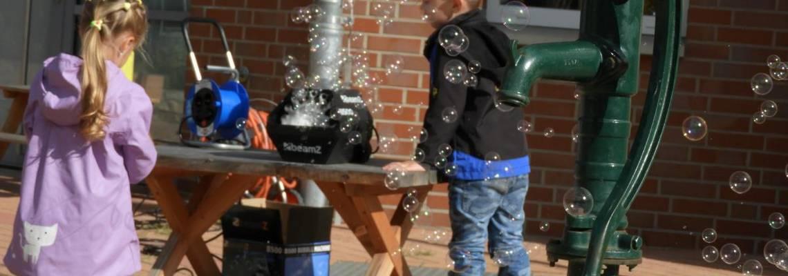 Zwei Kinder bestaunen die Seifenblasen