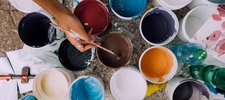 verschieden Farbtöpfe, aus denen die Hand einer Person mit einem Pinsel Farbe entnimmt ©Pixabay