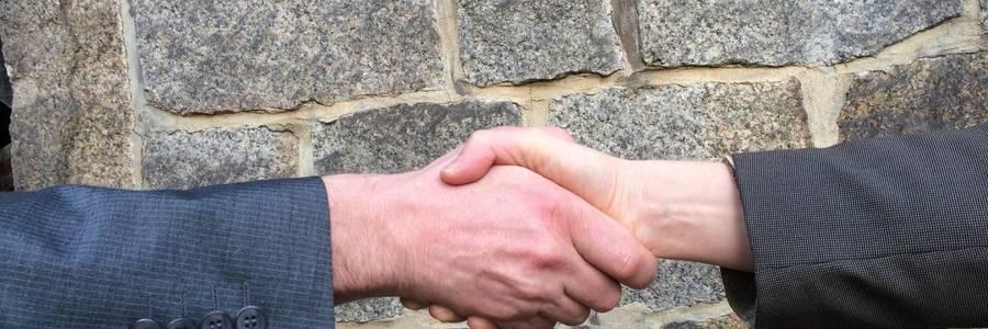 Zwei Hände schütteln sich, mit einer Backsteinmauer im Hintergrund
