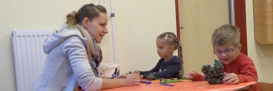 Eine Heilpädagogin spricht interessiert mit zwei Kindern